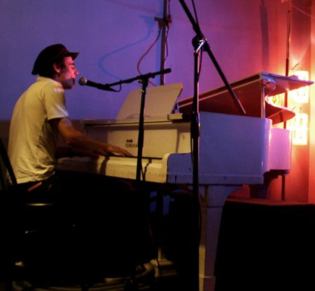 Max Gabriel performing with a white grand piano